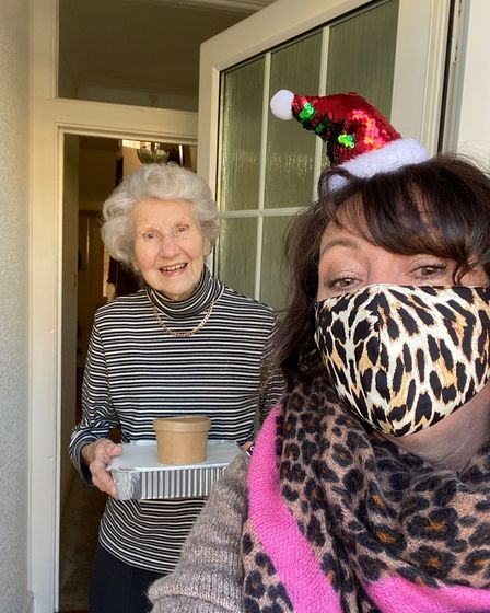 Residents receiving her Christmas meal from a volunteer
