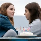 Two girls sitting at table with a cake on it