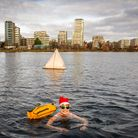 Swimmer with sunglasses and Santa hat floats in the reservoir.