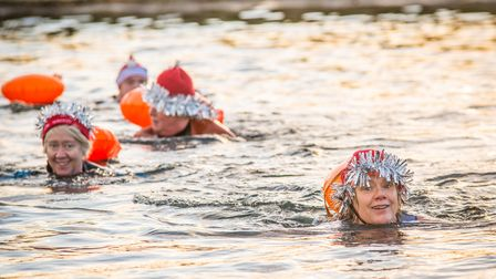 Several swimmers swim in the reservoir wearing Santa hats and tinsel.