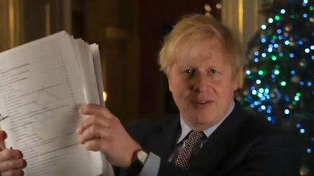 Boris Johnson holds up his Brexit agreement in a Christmas message