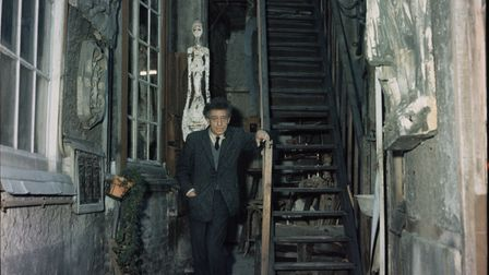 Alberto Giacometti stands in the stairwell to his house, where the walls are decorated with his sculptures