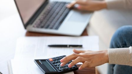 Businesswoman using calculator and laptop for budget cost money management strategy, female hands ca