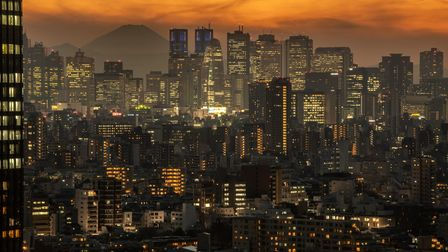 Mount Fuji is seen behind the city skyline at dusk on December 23, 2020