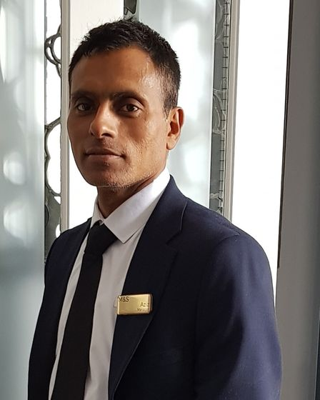 Marks and Spencer manager Azizur Rahmen stands in a suit.