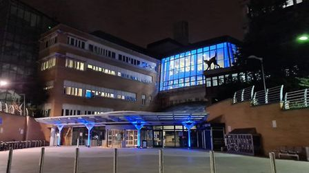 A picture of The Whittington Hospital lit up with blue lights.