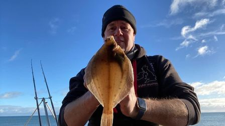 Marcus Ward with a dab fish, with bright blue skies behind him