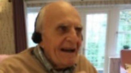 Old man smiling as he listens to headphones