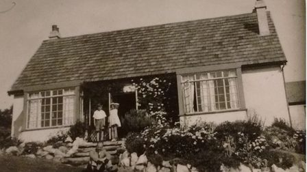 A girl and boy stood outside a bungalow called Kenwood in 1935