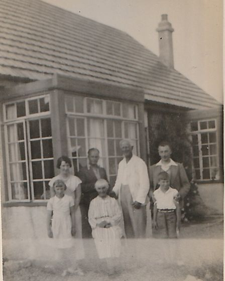 A family photo taken outside in a house in the 1930s