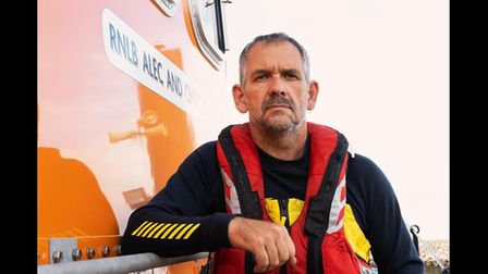 RNLI Torbay Coxswain Mark Criddle wearing a buoyancy aid and sat on a lifeboat