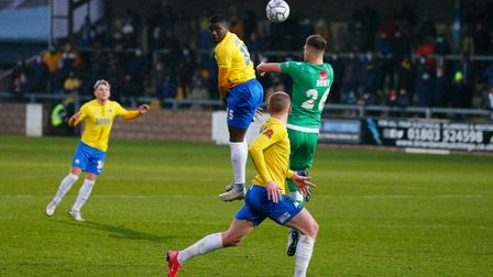 Josh Umerah of Torquay United wins the aerial challenge against Max Hunt of Yeovil Town during the