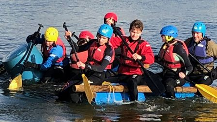 A group of young people wearing buoyancy aids and safety helmets, kayaking