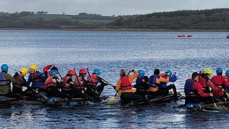 A large group of young people taking part in water-based kayak team-building activity