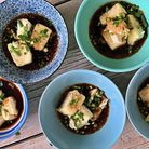 Five bowls of tofu in a dark broth