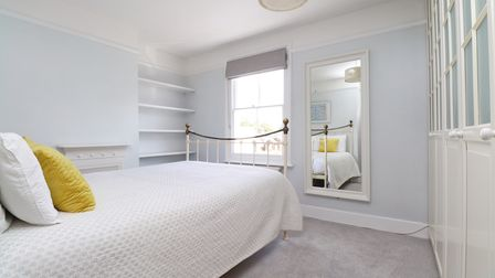 The master bedroom boasts a feature fireplace andfitted wardrobes.