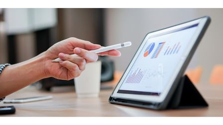 close up salesman employee hand using stylus pen to pointing on tablet screen to show company profit