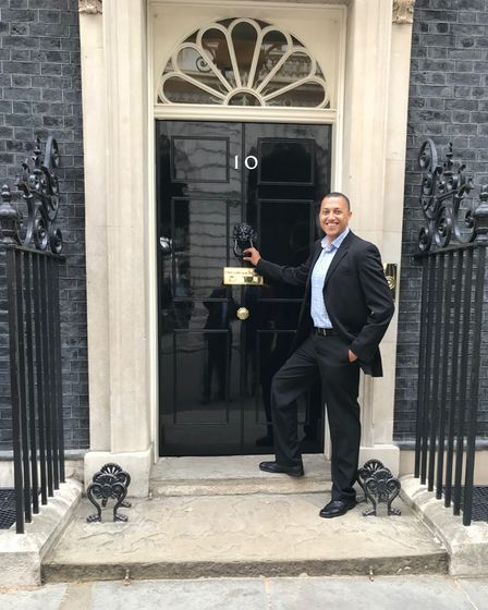 Aaron Henriques stands in front of the doors of 10 Downing Street in a suit.