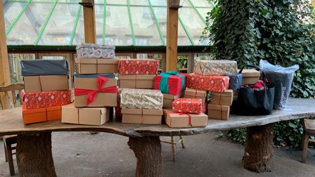 Colourfully wrapped shoeboxes displayed on wooden table.