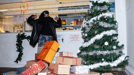 Akka member stands with thumbs up next to pile of wrapped shoeboxes filled with toiletries.