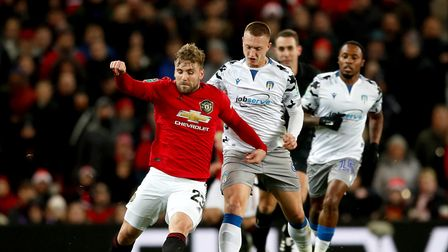 Manchester United's Luke Shaw (left) and Colchester United's Luke Norris battle for the ball during