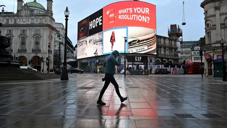 A pedestrian shelters from the rain as they walk across an almost deserted Piccadilly Circus as Britain enters its latest...