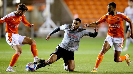Charlton Athletic's Akin Famewo (centre) battles for the ball with Blackpool's CJ Hamilton (right) a