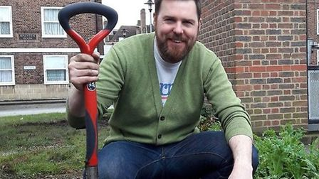 Cllr Jon Burke stands with a shovel in hand.
