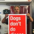 """DavidBuonaguidi, also known as Real Hackney Dave, holds up one of his prints which reads: """"Dogs don't do discos."""""""