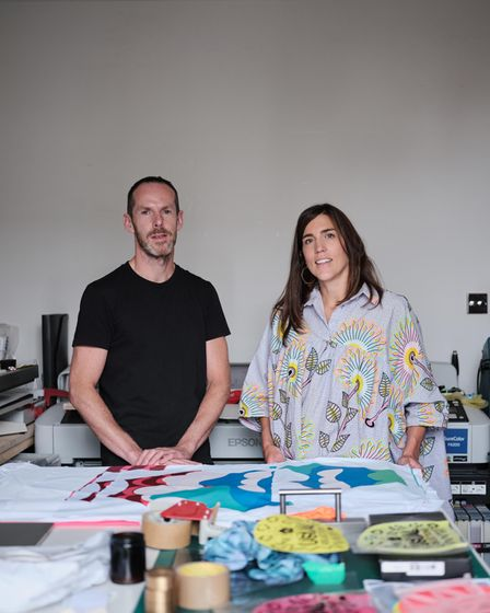 Founders of Usual Objections stand in front of designs and sewing equiptment