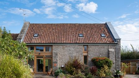 stone barn conversion with French doors and surrounding windows on the left side and shrubs and wooden chairs in the...