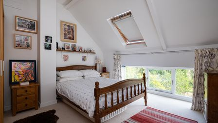 double bedroom with double bed recessed into back wall with small windows at ground level behind and a sloping ceiling...