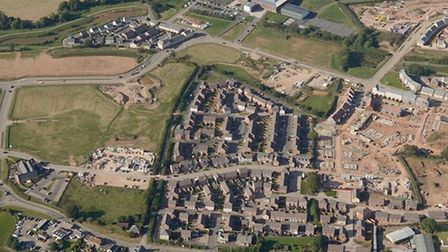 An aerial photograph of Cranbrook Town Centre with the pub and roundabout to the south, education campus to the north and housing east and west. The town centre is the square area of open land left of centre