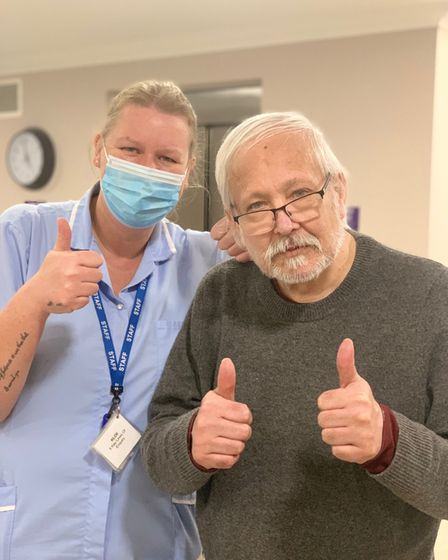 A resident and healthcare professional give thumbs up to vaccine