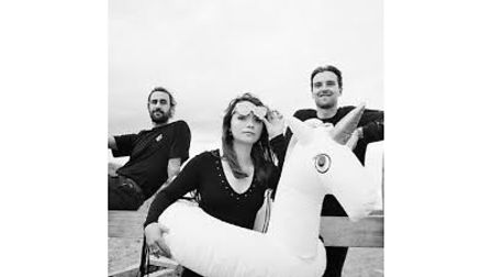 The three members of the band Soot Sprite, with a woman in the foreground with an inflatable unicorn