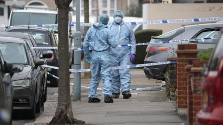 Forensic officers at the scene in Tavistock Gardens, Ilford, east London after two men died at a pro