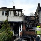 Fire damaged house with fire brigade outside
