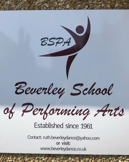 A plaque with the Beverley School logo and additional information.