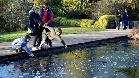 Children enjoy breaking up the ice which had formed on top of