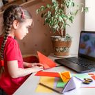 Cute little elementary schoolgirl doing origami fish with folded color paper looking video on laptop
