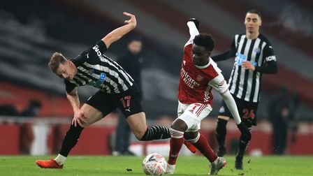 Arsenal's Bukayo Saka (right) and Newcastle United's Emil Krafth (left) battle for the ball during t