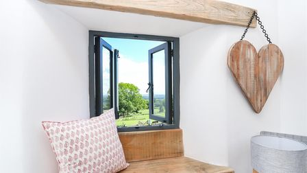 Small open window in a house with a countryside view. Windowsill seat underneath with decorative cushion.