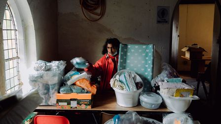 Woman sorts through donated baby clothes and resources.