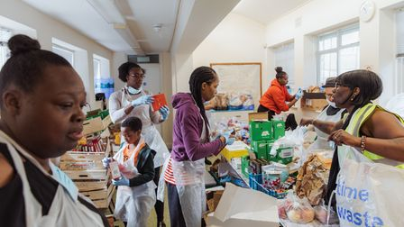 Volunteers from Hackney charity Children With Voices sortsupplies at one of itsfood hubs.