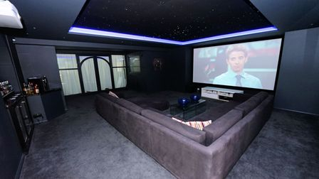 a cinema room with grey velour l-shaped sofa in front of huge screen, window in background and grey carpet