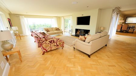drawing room with parquet floor, three sofas arranged around a beige rug and fireplace with TV on wall above and large...