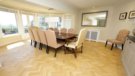 dining room with large laquered dark wood table with ten cream upholstered dining chairs, parquet floor and a windowed...