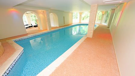 pool room with long thin blue pool in the middle with tiled sides, pillars, archway to changing area and windows at the...