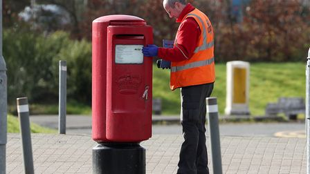 A Royal Mail postman empties a postbox near the SEC Centre in Glasgow which is being turned into a t