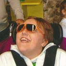 Girl in wheelchair wearing sunglasses